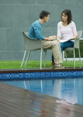Man and woman talking by poolside LANG_EVOIMAGES