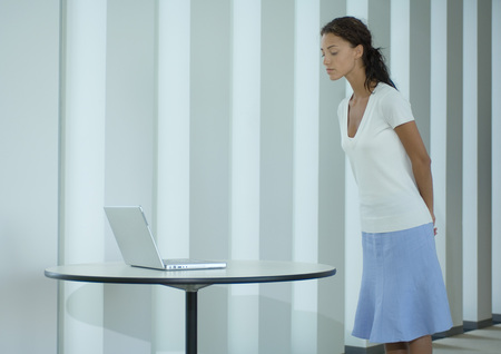 Woman standing, looking at laptop on table