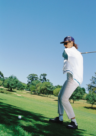 Mature woman playing golf LANG_EVOIMAGES
