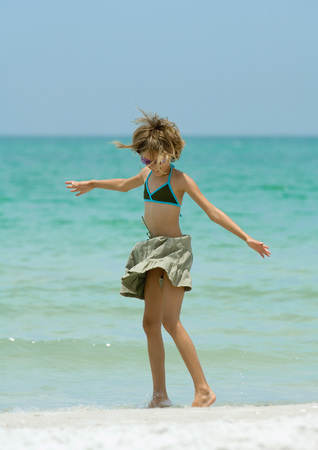 over the edge: Girl standing in wind on beach