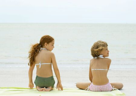 distractions: Two girls sitting on beach towel, rear view