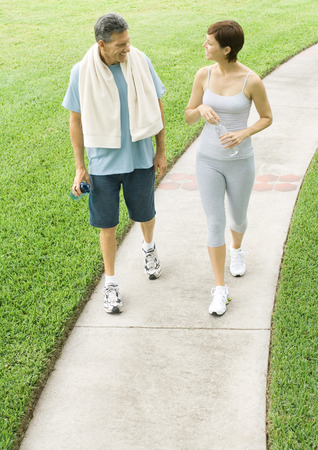 Mature couple walking on path after workout