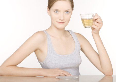 grey eyed: Woman holding up glass of juice