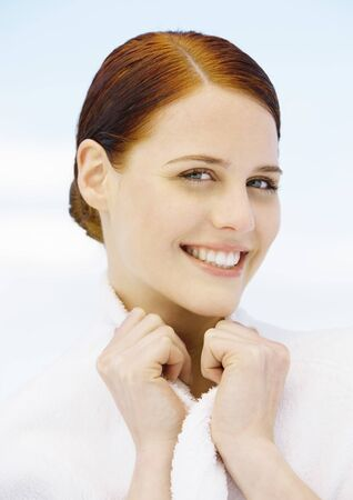 greased: Woman smiling and holding collar of bathrobe