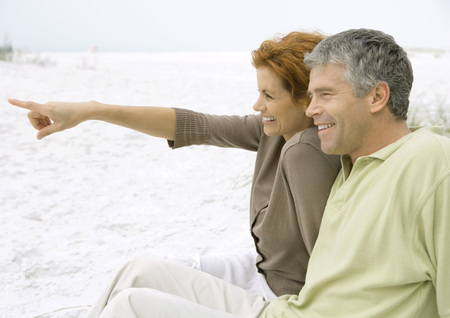Mature couple sitting on beach, side view