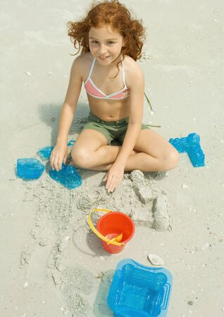 Girl playing in sand on beach LANG_EVOIMAGES
