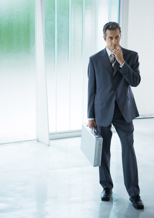 Businessman standing in lobby, holding briefcase