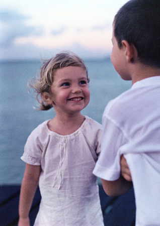 front facing: Girl smiling at boy near sea LANG_EVOIMAGES