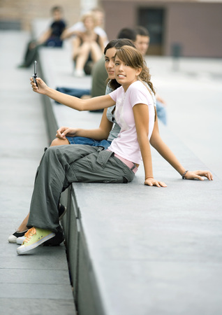 distractions: Two teenage girls sitting on bench in urban setting, taking photo with cell phone