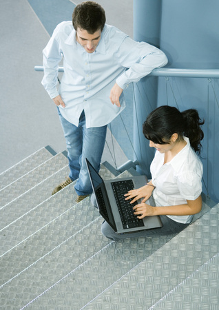 Two colleagues talking, one sitting on stairs with laptop LANG_EVOIMAGES