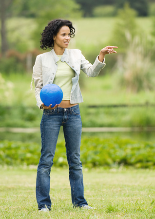 Woman holding ball and pointing out of frame