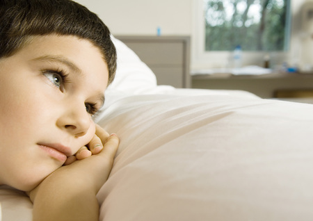 repose: Child lying in bed, cropped view of head