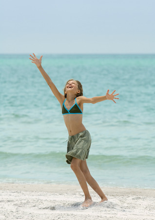Girl running with arms up on beach