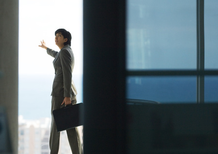 Woman standing with briefcase, next to bay window with arm out, looking over shoulder LANG_EVOIMAGES