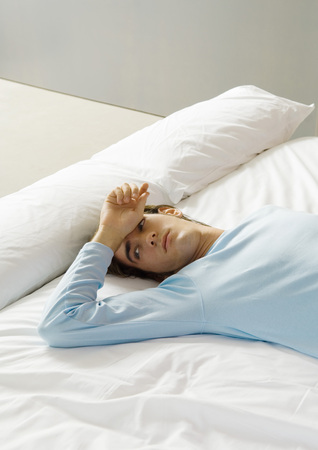 unease: Man lying on bed with hand on forehead