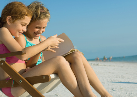 turning the page: Girls reading book together on beach