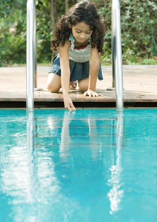 Girl crouching by edge of pool, touching surface of water