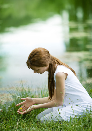 Girl kneeling in grass with hands cupped
