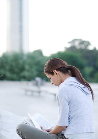 oneself: Young woman reading outdoors on college campus LANG_EVOIMAGES