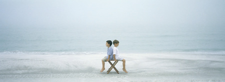 niño parado: On beach, two boys sitting back to back on stool