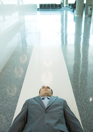 burned out: Businessman lying down on floor in airport LANG_EVOIMAGES
