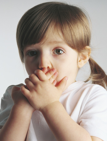 Little girl covering mouth, portrait LANG_EVOIMAGES