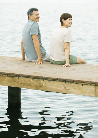 Couple sitting on edge of dock LANG_EVOIMAGES