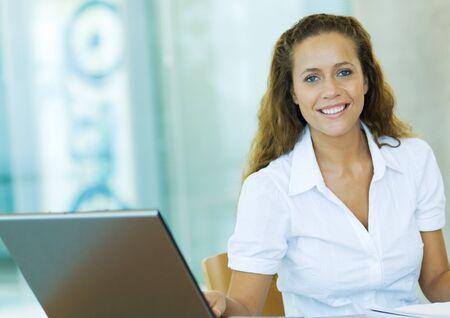 Businesswoman sitting by laptop, smiling, portrait