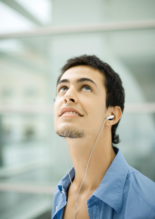 Young man listening to earphones, looking up LANG_EVOIMAGES
