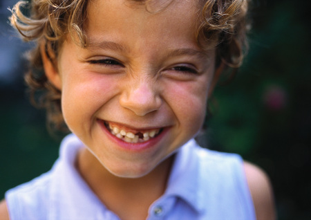 Girl with missing tooth smiling