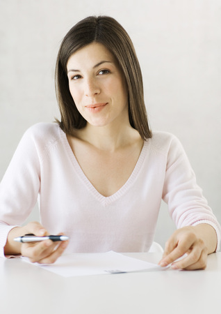 Woman sitting with pen and document LANG_EVOIMAGES