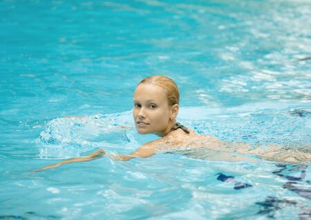 Young woman swimming in pool LANG_EVOIMAGES