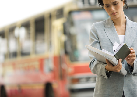 Businesswoman looking at agenda in street