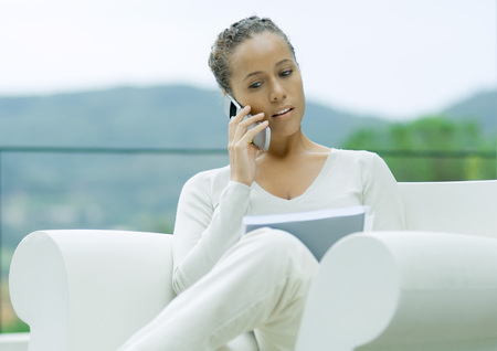 Woman sitting outdoors in armchair, using cell phone and looking at document