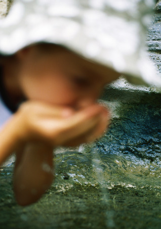 tiredness: Girl drinking water from cupped hands LANG_EVOIMAGES