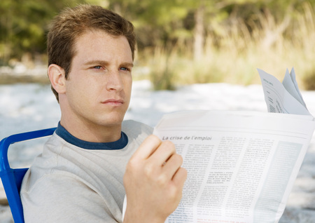 distractions: Man looking up from newspaper on beach LANG_EVOIMAGES