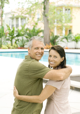 sumptuousness: Couple standing in front of pool, smiling