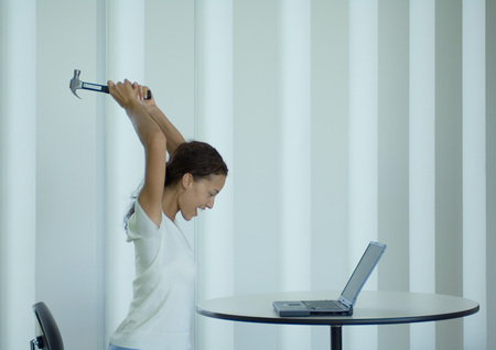Woman shouting and swinging hammer at laptop