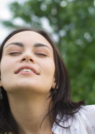 Woman closing eyes, close-up