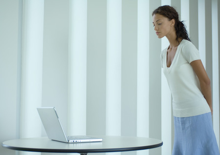 Woman standing, looking down at laptop