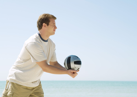 Man serving volleyball on beach