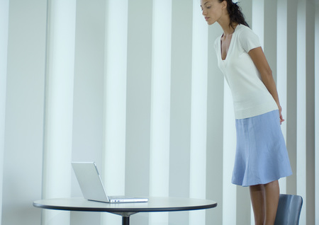 Woman standing on chair, looking down at laptop