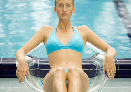 Woman in bikini sitting in transparent chair by pool LANG_EVOIMAGES