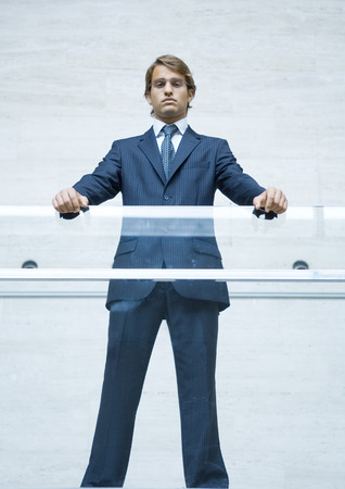 Businessman standing with hands resting on transparent guard rail, portrait, low angle view