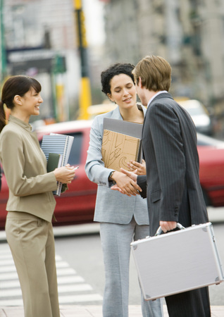 Business people shaking hands on side of street