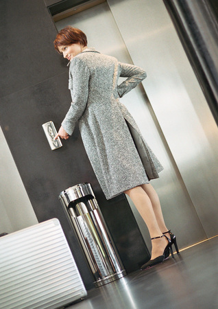 Woman standing in front of elevator pushing button, low angle view LANG_EVOIMAGES