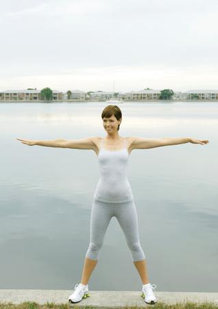 Woman exercising, lakeside