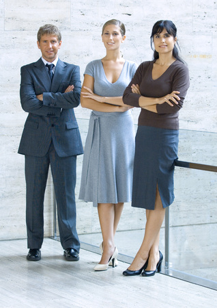 Three business executives standing with arms folded, full length portrait