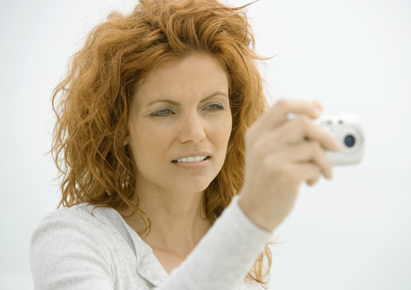 Woman holding up camera, squinting