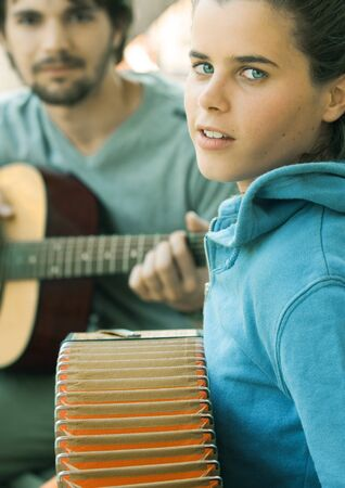 Young woman playing accordian and young man playing guitar